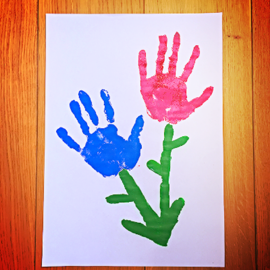 A child's painting featuring a blue and a pink hand impression, in the shape of a couple of flowers.